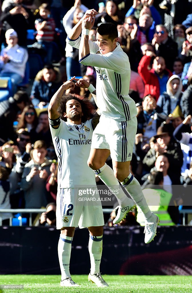 Real Madrid's Portuguese forward Cristiano Ronaldo (R) celebrates past Real Madrid's Brazilian defender Marcelo after scoring during the Spanish league football match Real Madrid CF vs Granada FC at the Santiago Bernabeu stadium in Madrid on January 7, 2017. / AFP / GERARD