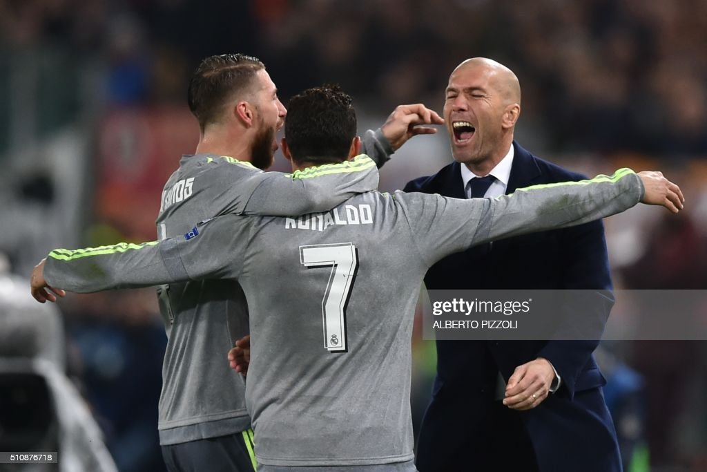 TOPSHOT - Real Madrid's Portuguese forward Cristiano Ronaldo (C) celebrates with Real Madrid's defender Sergio Ramos and Real Madrid's French coach Zinedine Zidane after scoring during the UEFA Champions League football match AS Roma vs Real Madrid on Frebruary 17, 2016 at the Olympic stadium in Rome. AFP PHOTO / ALBERTO PIZZOLI