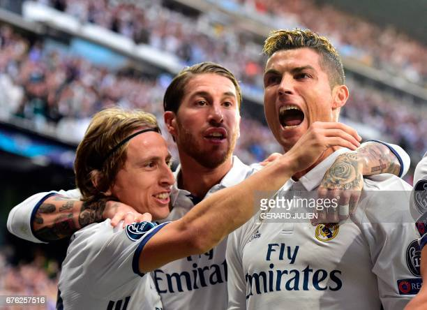 Real Madrid's Portuguese forward Cristiano Ronaldo celebrates with Real Madrid's Croatian midfielder Luka Modric and Real Madrid's defender Sergio...
