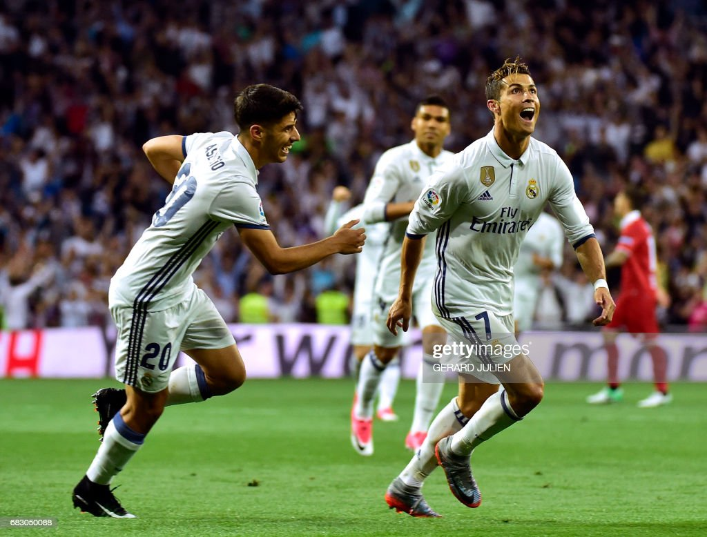 Real Madrid's Portuguese forward Cristiano Ronaldo celebrates with Real Madrid's midfielder Marco Asensio after scoring during the Spanish league football match Real Madrid CF vs Sevilla FC at the Santiago Bernabeu stadium in Madrid on May 14, 2017. /