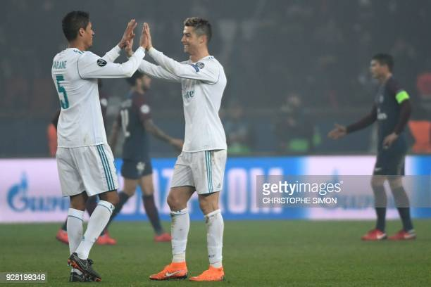 Real Madrid's Portuguese forward Cristiano Ronaldo celebrates with Real Madrid's French defender Raphael Varane after winning the UEFA Champions...