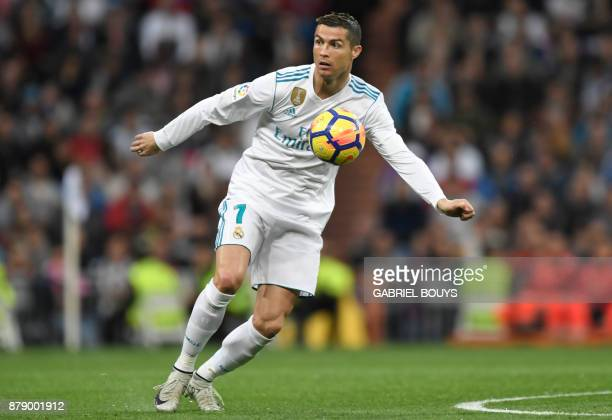TOPSHOT Real Madrid's Portuguese forward Cristiano Ronaldo controls the ball during the Spanish league football match Real Madrid CF against Malaga...