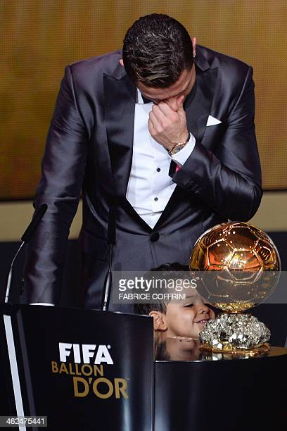 Real Madrid's Portuguese forward Cristiano Ronaldo cries as he accepts the 2013 FIFA Ballon d'Or award for player of the year with his son Cristiano...
