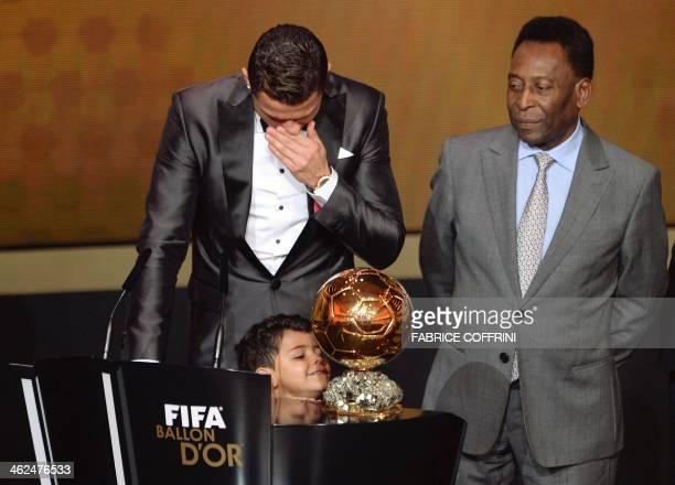 Real Madrid's Portuguese forward Cristiano Ronaldo cries next to his son Cristiano Ronaldo Junior and Brazilian football legend Pele after winning...