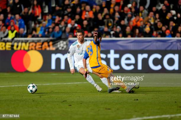 Real Madrid's Portuguese forward Cristiano Ronaldo dribbles past Apoel's Greek defender Praxitelis Vouros during the UEFA Champions League Group H...