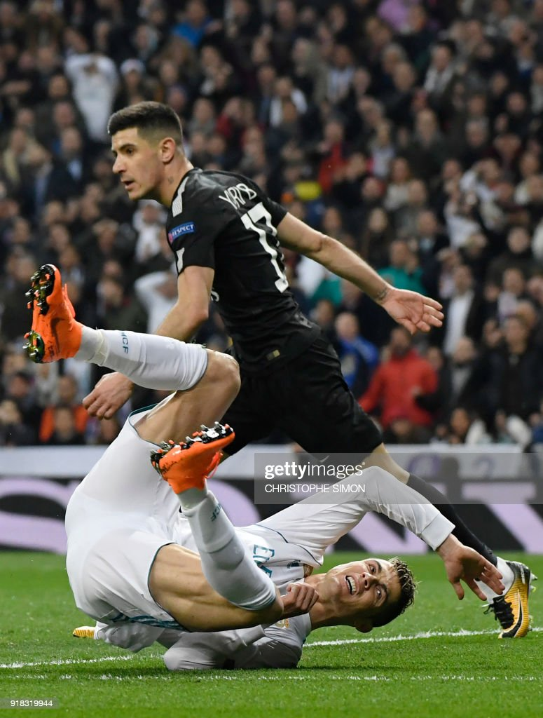 Real Madrid's Portuguese forward Cristiano Ronaldo (bottom) falls down beside Paris Saint-Germain's Spanish defender Yuri Berchiche during the UEFA Champions League round of sixteen first leg football match Real Madrid CF against Paris Saint-Germain (PSG) at the Santiago Bernabeu stadium in Madrid on February 14, 2018. /