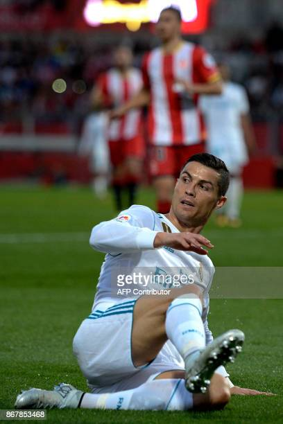 Real Madrid's Portuguese forward Cristiano Ronaldo falls to the field after a goal by Girona during the Spanish league football match Girona FC vs...
