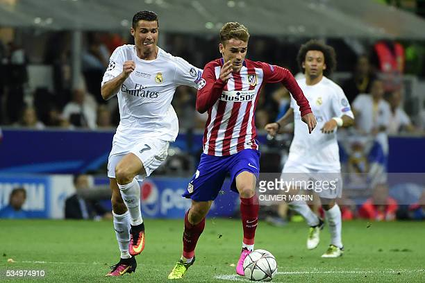 Real Madrid's Portuguese forward Cristiano Ronaldo fights for the ball with Atletico Madrid's French forward Antoine Griezmann during the UEFA...