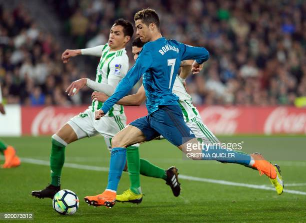Real Madrid's Portuguese forward Cristiano Ronaldo fights for the ball with Real Betis' Spanish defender Marc Bartra during the Spanish league...