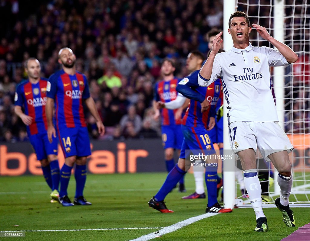 Real Madrid's Portuguese forward Cristiano Ronaldo (R) gestures after missing a goal during the Spanish league football match FC Barcelona vs Real Madrid CF at the Camp Nou stadium in Barcelona on December 3, 2016. / AFP / JOSEP