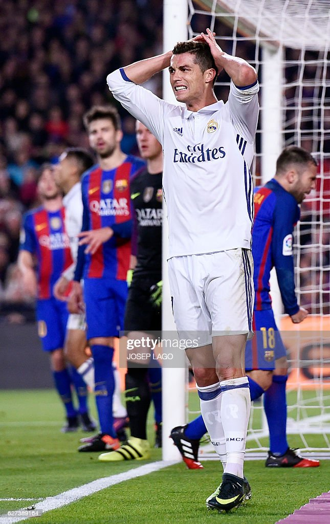 Real Madrid's Portuguese forward Cristiano Ronaldo (C) gestures after missing a goal during the Spanish league football match FC Barcelona vs Real Madrid CF at the Camp Nou stadium in Barcelona on December 3, 2016. / AFP / JOSEP