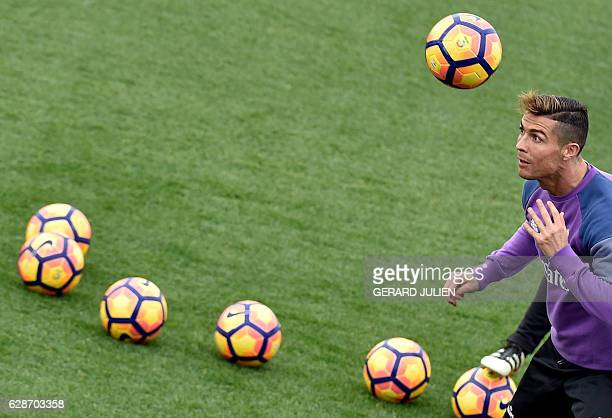 Real Madrid's Portuguese forward Cristiano Ronaldo heads a ball during a training session at Valdebebas training ground in Madrid on December 9 on...