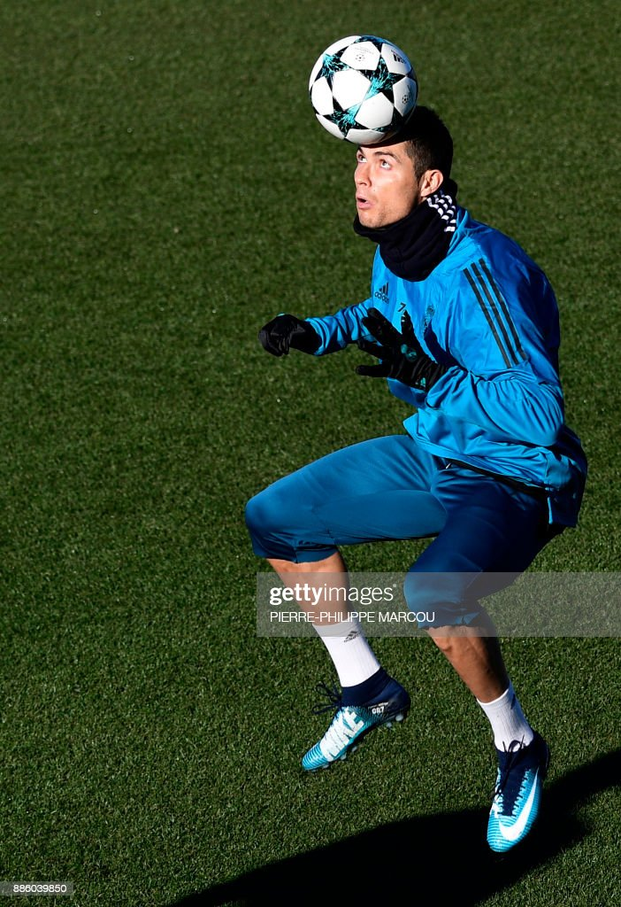 Real Madrid's Portuguese forward Cristiano Ronaldo heads the ball during a training session at Valdebebas Sport City in Madrid on December 5, 2017 on the eve of their Champions' League match against Borussia Dortmund. /