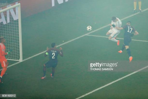 TOPSHOT Real Madrid's Portuguese forward Cristiano Ronaldo heads the ball and scores the opening goal during the UEFA Champions League round of 16...