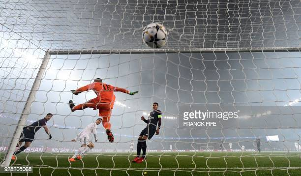 TOPSHOT Real Madrid's Portuguese forward Cristiano Ronaldo heads the ball and scored a goal despite Paris SaintGermain's French goalkeeper Alphonse...