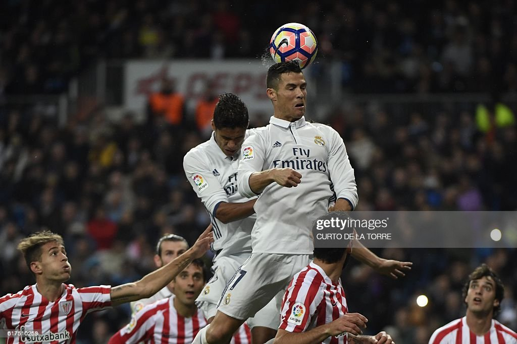 Real Madrid's Portuguese forward Cristiano Ronaldo (top R) heads the ball during the Spanish league football match between Real Madrid CF and Athletic Club Bilbao at the Santiago Bernabeu stadium in Madrid on October 23, 2016. / AFP / CURTO