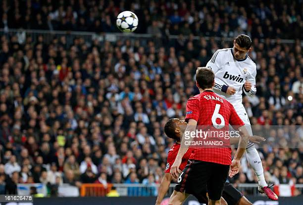 Real Madrid's Portuguese forward Cristiano Ronaldo heads the ball to score during the UEFA Champions League round of 16 first leg football match Real...
