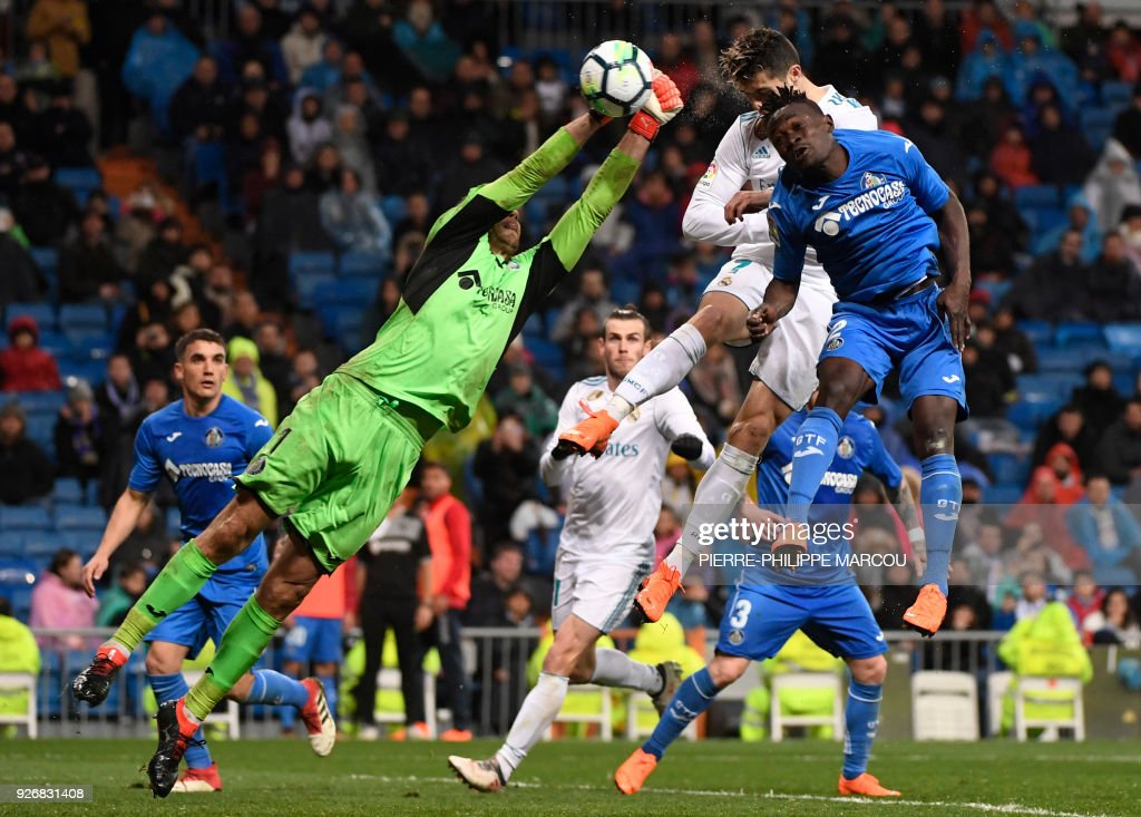 TOPSHOT - Real Madrid's Portuguese forward Cristiano Ronaldo (top) heads the ball to score a goal during the Spanish league football match Real Madrid CF against Getafe CF at the Santiago Bernabeu stadium in Madrid on March 3, 2018. /