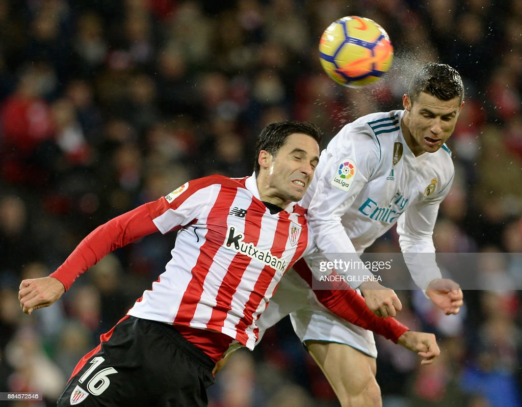 TOPSHOT - Real Madrid's Portuguese forward Cristiano Ronaldo (R) heads the ball with Athletic Bilbao's Spanish defender Xabier Etxeita during the Spanish league football match Athletic Club Bilbao vs Real Madrid CF at the San Mames stadium in Bilbao on December 2, 2017. /