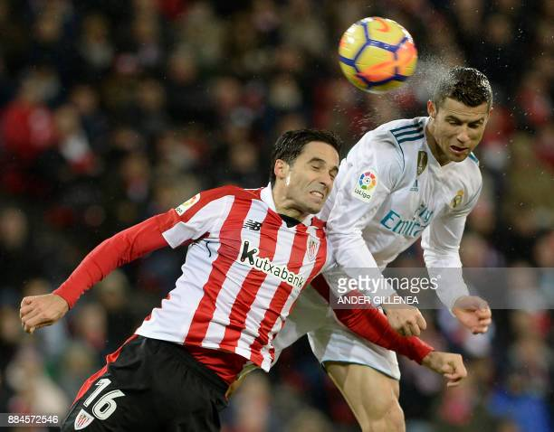 TOPSHOT Real Madrid's Portuguese forward Cristiano Ronaldo heads the ball with Athletic Bilbao's Spanish defender Xabier Etxeita during the Spanish...