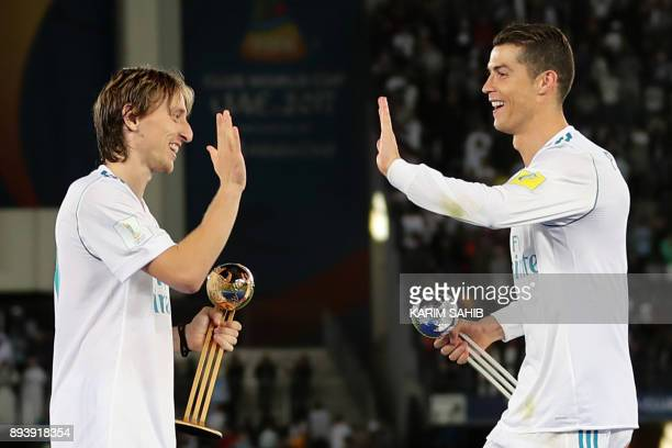 Real Madrid's Portuguese forward Cristiano Ronaldo holding his 2017 FIFA Club World Cup Silver Ball award celebrates with his teammate Luka Modric...