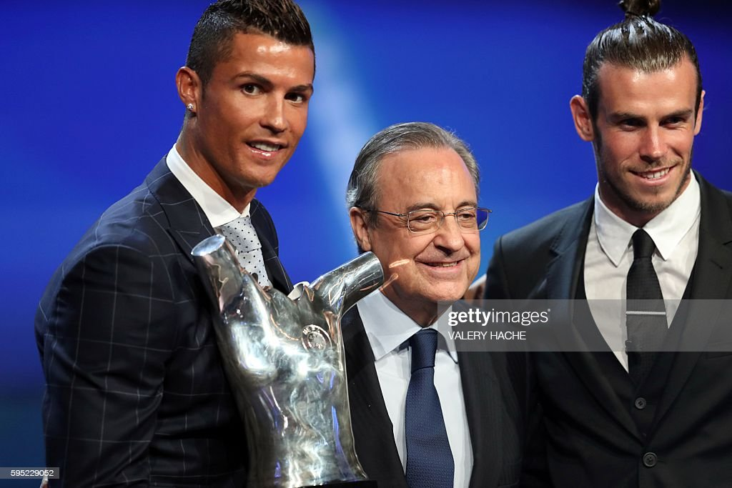 Real Madrid's Portuguese forward Cristiano Ronaldo (L) holds his trophy of Best Men's player in Europe as he poses with Real Madrid President Florentino Perez (C) and Real Madrid's Welsh forward Gareth Bale at the end of the UEFA Champions League Group stage draw ceremony, on August 25, 2016 in Monaco. / AFP / VALERY