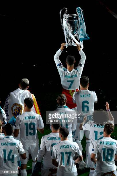 Real Madrid's Portuguese forward Cristiano Ronaldo holds the trophy at the Santiago Bernabeu stadium in Madrid on May 27 2018 during a victory...