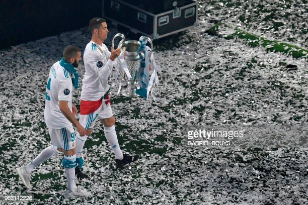 Real Madrid's Portuguese forward Cristiano Ronaldo holds the trophy next to Real Madrid's French forward Karim Benzema at the Santiago Bernabeu...