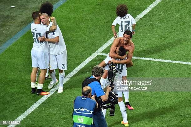 Real Madrid's Portuguese forward Cristiano Ronaldo hugs team mate Brazilian midfielder Casemiro as Real Madrid's Spanish forward Jese Rodriguez hugs...