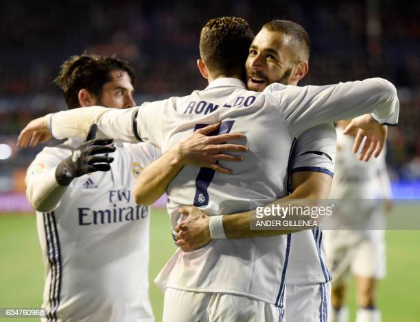 Real Madrid's Portuguese forward Cristiano Ronaldo is congratulated by teammate French forward Karim Benzema after scoring his team's first goal...