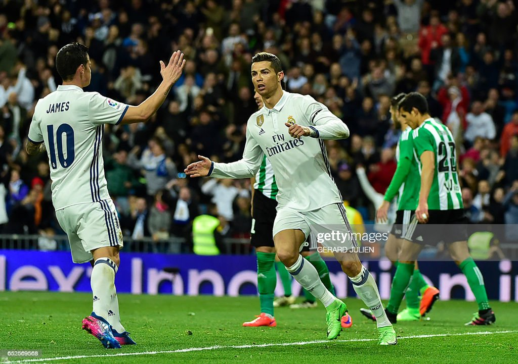 TOPSHOT - Real Madrid's Portuguese forward Cristiano Ronaldo (R) is congratulated by Real Madrid's Colombian midfielder James Rodriguez after scoring a goal during the Spanish league footbal match Real Madrid CF vs Real Betis at the Santiago Bernabeu stadium in Madrid on March 12, 2017. /