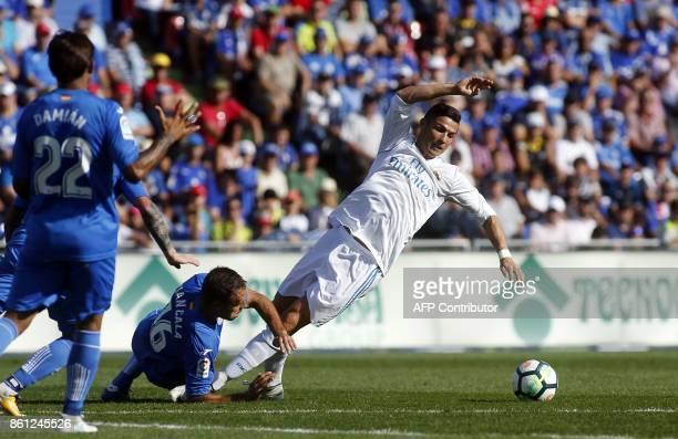 Real Madrid's Portuguese forward Cristiano Ronaldo is fouled by Getafe's Spanish defender Juan Cala during the Spanish league football match Getafe...
