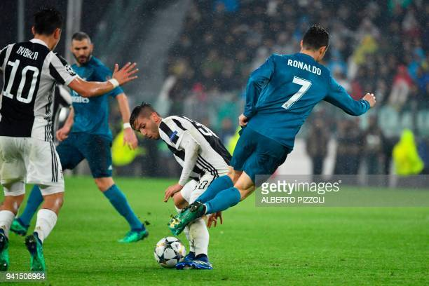 Real Madrid's Portuguese forward Cristiano Ronaldo is tackled by Juventus' midfielder from Uruguay Rodrigo Bentancur during the UEFA Champions League...