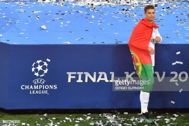 Real Madrid's Portuguese forward Cristiano Ronaldo is wrapped into a Portuguese flag as he celebrates after his team won the UEFA Champions League...