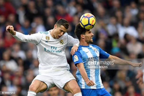 Real Madrid's Portuguese forward Cristiano Ronaldo jumps for the ball with Malaga's Spanish midfielder Adrian Gonzalez Morales during the Spanish...