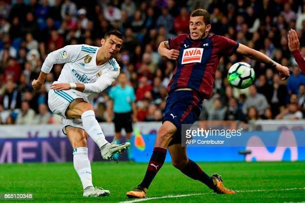 Real Madrid's Portuguese forward Cristiano Ronaldo kicks the ball past Eibar's Spanish midfielder Christian Rivera during the Spanish league football...