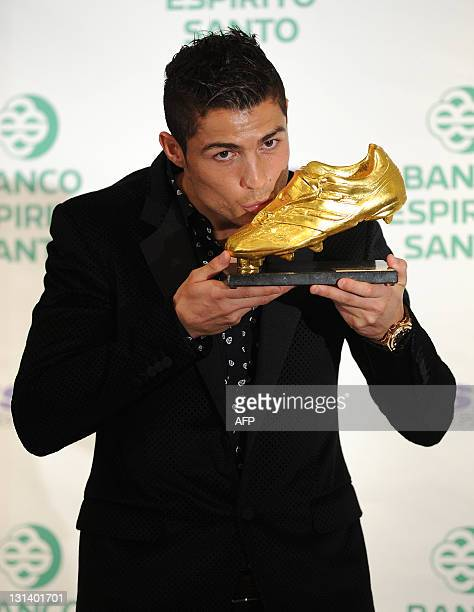 Real Madrid's Portuguese forward Cristiano Ronaldo kisses his 'Golden Boot 2011' award presented to Europe's best goal scorer on November 04 in...