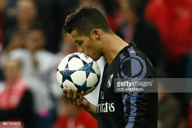 TOPSHOT Real Madrid's Portuguese forward Cristiano Ronaldo kisses the ball bvefore taking a free kick during the UEFA Champions League 1st leg...