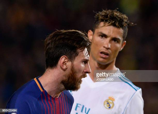 TOPSHOT Real Madrid's Portuguese forward Cristiano Ronaldo looks at Barcelona's Argentinian forward Lionel Messi during the Spanish league football...
