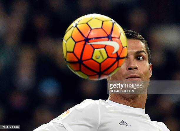 TOPSHOT Real Madrid's Portuguese forward Cristiano Ronaldo looks at the ball during the Spanish league football match Real Madrid CF vs RC Deportivo...