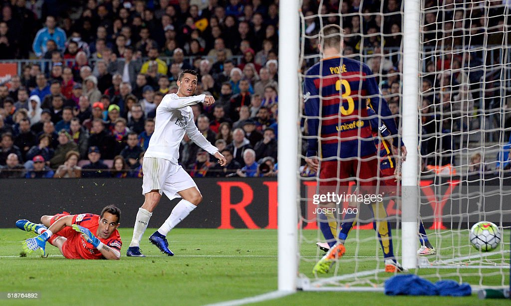 Real Madrid's Portuguese forward Cristiano Ronaldo (L) looks at the ball after scoring a goal during the Spanish league 'Clasico' football match FC Barcelona vs Real Madrid CF at the Camp Nou stadium in Barcelona on April 2, 2016. / AFP / JOSEP