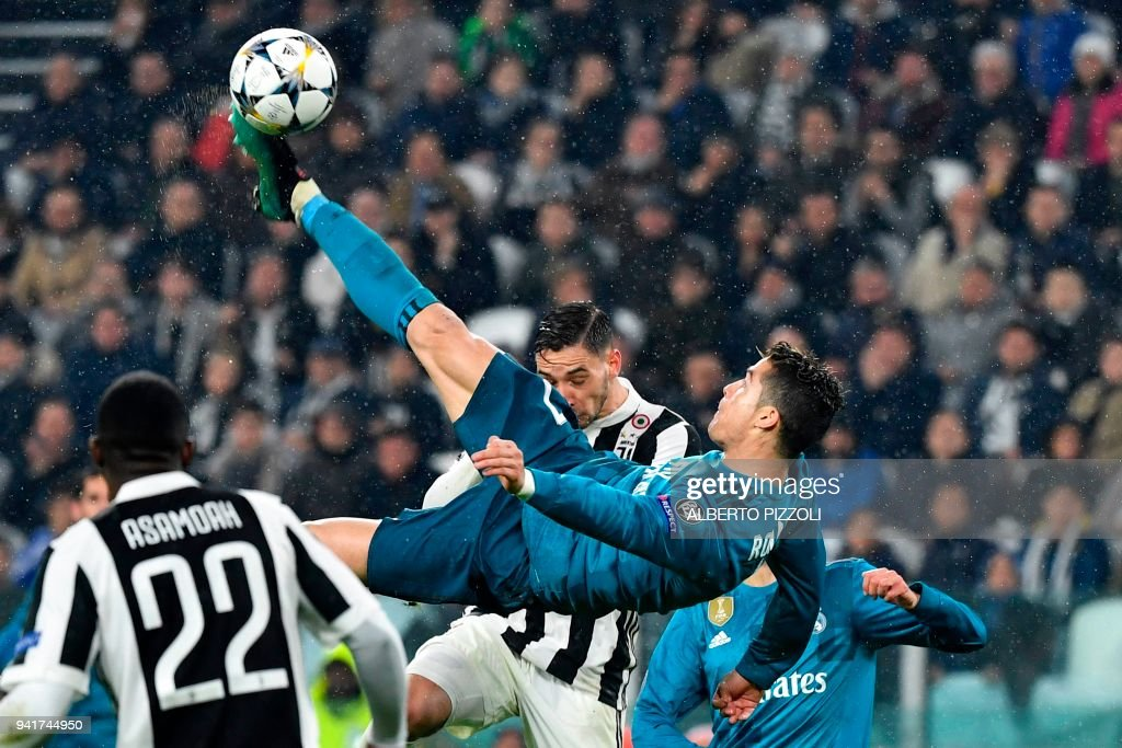 TOPSHOT - Real Madrid's Portuguese forward Cristiano Ronaldo (C) overhead kicks and scores during the UEFA Champions League quarter-final first leg football match between Juventus and Real Madrid at the Allianz Stadium in Turin on April 3, 2018. / AFP PHOTO / Alberto PIZZOLI