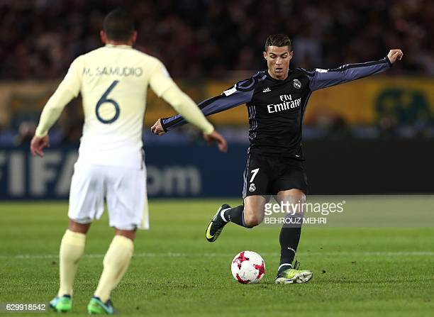 Real Madrid's Portuguese forward Cristiano Ronaldo passes Club America's defender Miguel Samudio during the Club World Cup semifinal football match...
