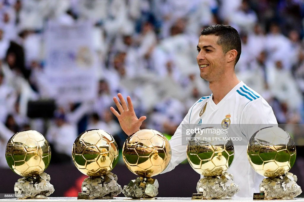 Real Madrid's Portuguese forward Cristiano Ronaldo poses with his five Ballon d'Or trophies ahead of the Spanish league football match between Real Madrid and Sevilla at the Santiago Bernabeu Stadium in Madrid on December 9, 2017. /