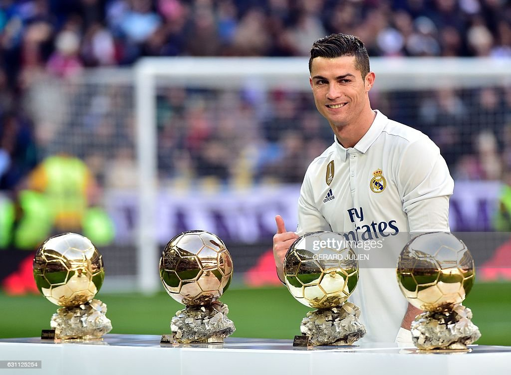 TOPSHOT - Real Madrid's Portuguese forward Cristiano Ronaldo poses with his four Ballon d'Or France Football trophies before the Spanish league football match Real Madrid CF vs Granada FC at the Santiago Bernabeu stadium in Madrid on January 7, 2017. / AFP / GERARD