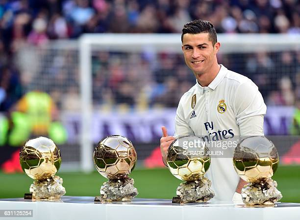TOPSHOT Real Madrid's Portuguese forward Cristiano Ronaldo poses with his four Ballon d'Or France Football trophies before the Spanish league...