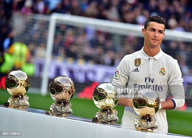 Real Madrid's Portuguese forward Cristiano Ronaldo poses with his four Ballon d'Or France Football trophies before the Spanish league football match...