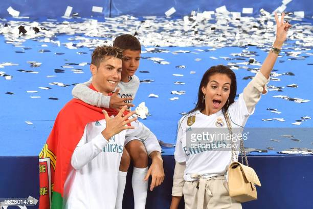 Real Madrid's Portuguese forward Cristiano Ronaldo poses with his girlfriend Georgina Rodriguez and his son Cristiano Jr after his team won the UEFA...