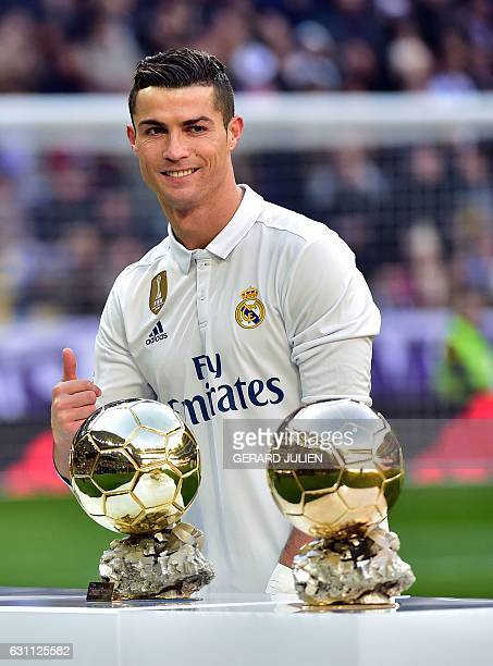Real Madrid's Portuguese forward Cristiano Ronaldo poses with two of his four Ballon d'Or France Football trophies before the Spanish league football...