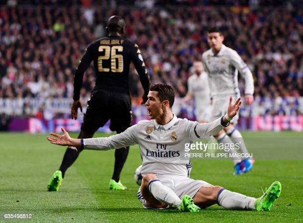 Real Madrid's Portuguese forward Cristiano Ronaldo protests as he sits on the field during the UEFA Champions League round of 16 first leg football...